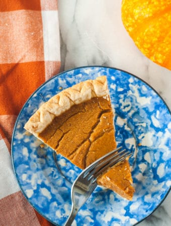 Pumpkin pie being sliced with a fork on a blue plate