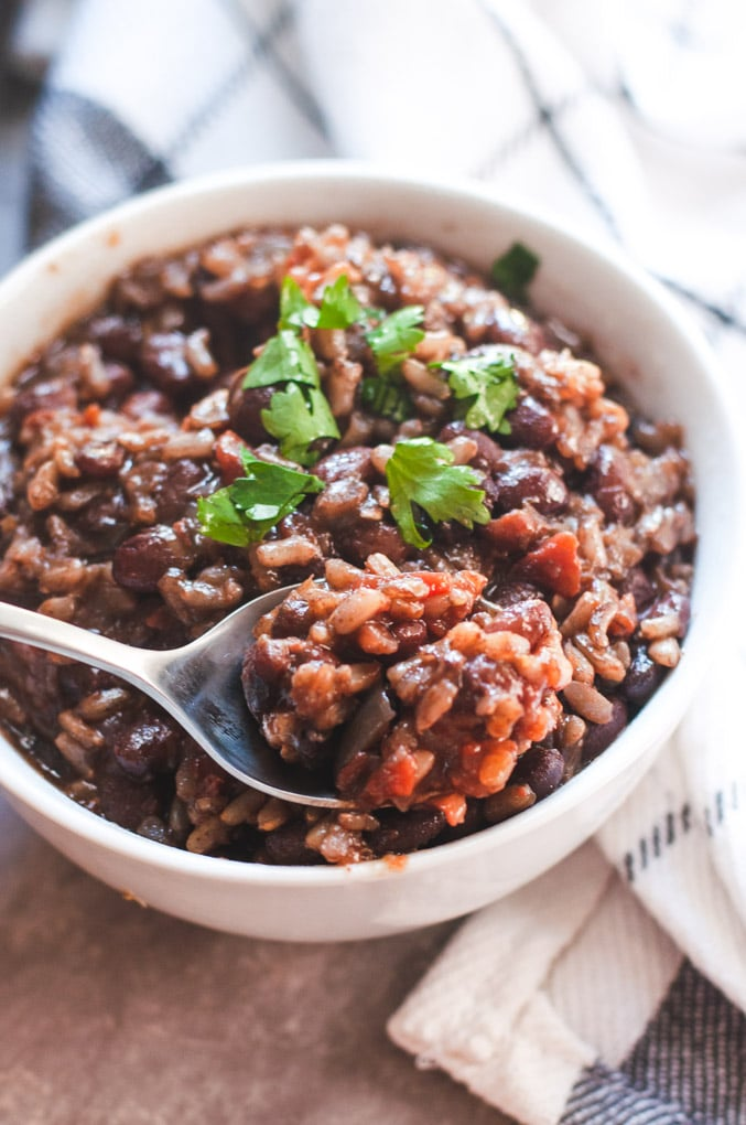 Spoonful of black beans and rice on a bowl of rice and beans; topped with cilantro