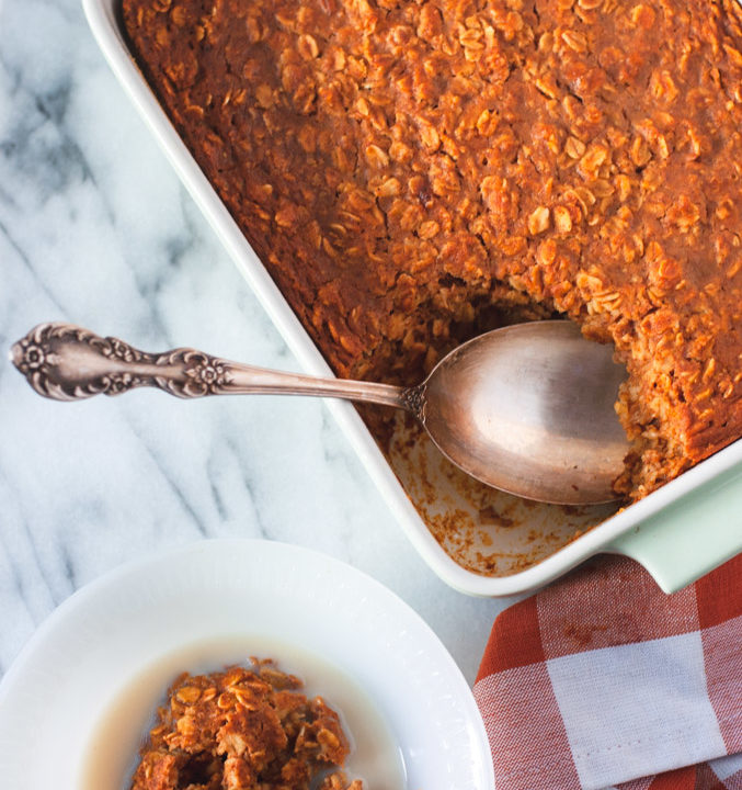 Pumpkin oatmeal in a bowl and in a baking dish with a spoon