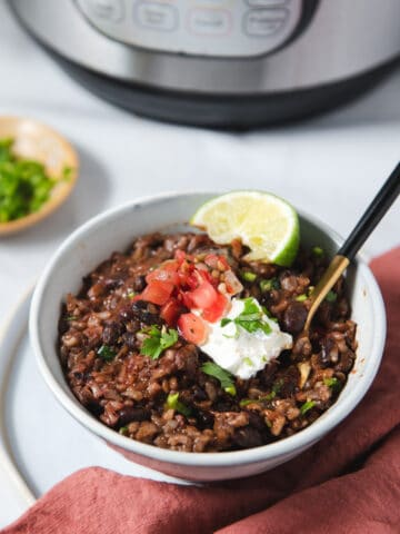 Side view of bowl of rice and beans topped with sour cream, salsa and a lime wedge