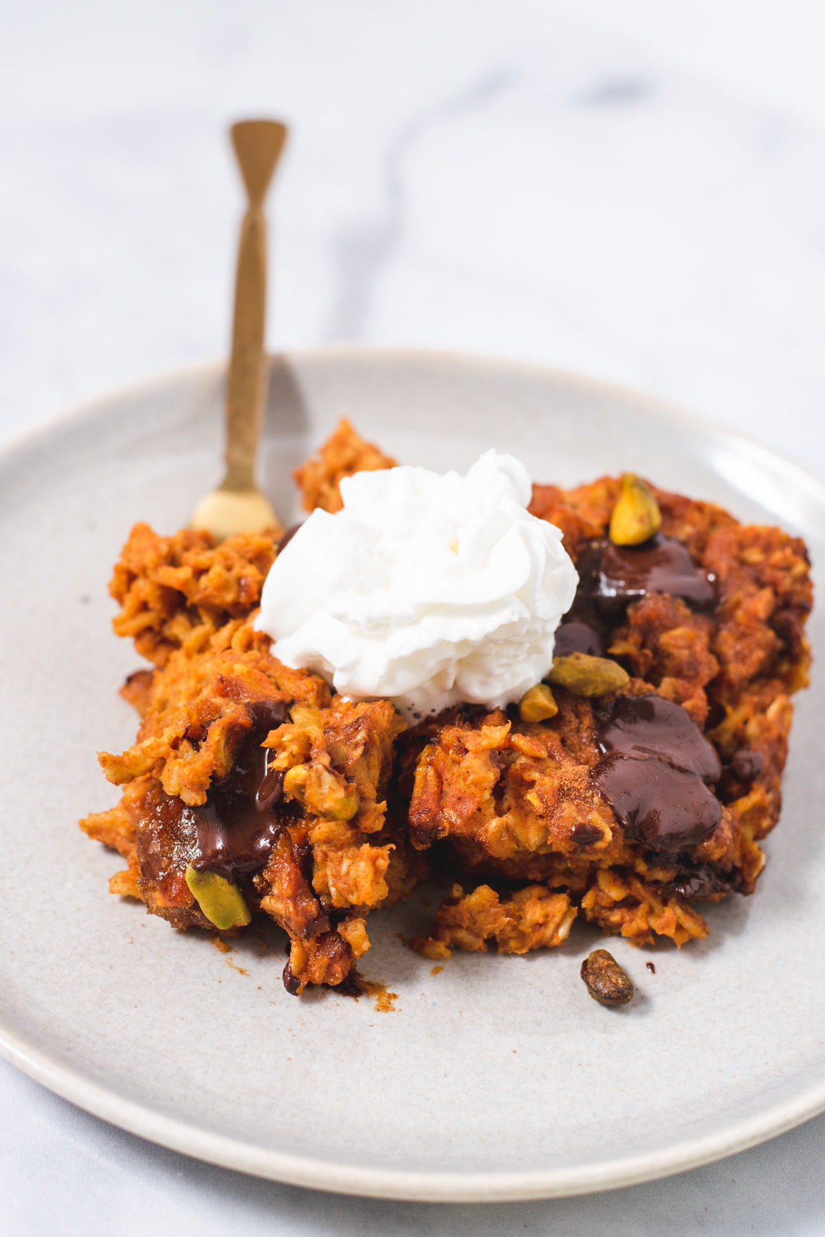 Serving of pumpkin oatmeal on a gray plate topped with whipped cream