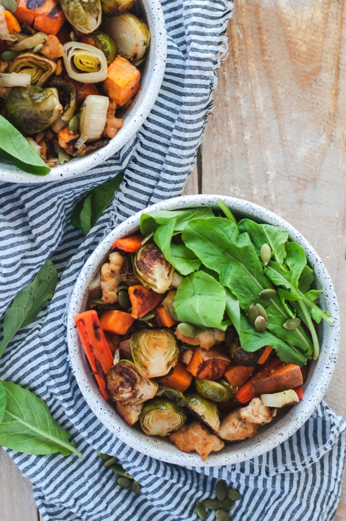 Overhead view of roasted fall vegetables and tempeh in a bowl with arugula and pumpkin seeds