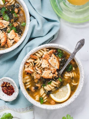 Overhead view of white bowl with chickpea noodle soup and lemon wedge