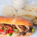 Vegetarian mushroom philly cheesesteak with chips and french onion dip in background