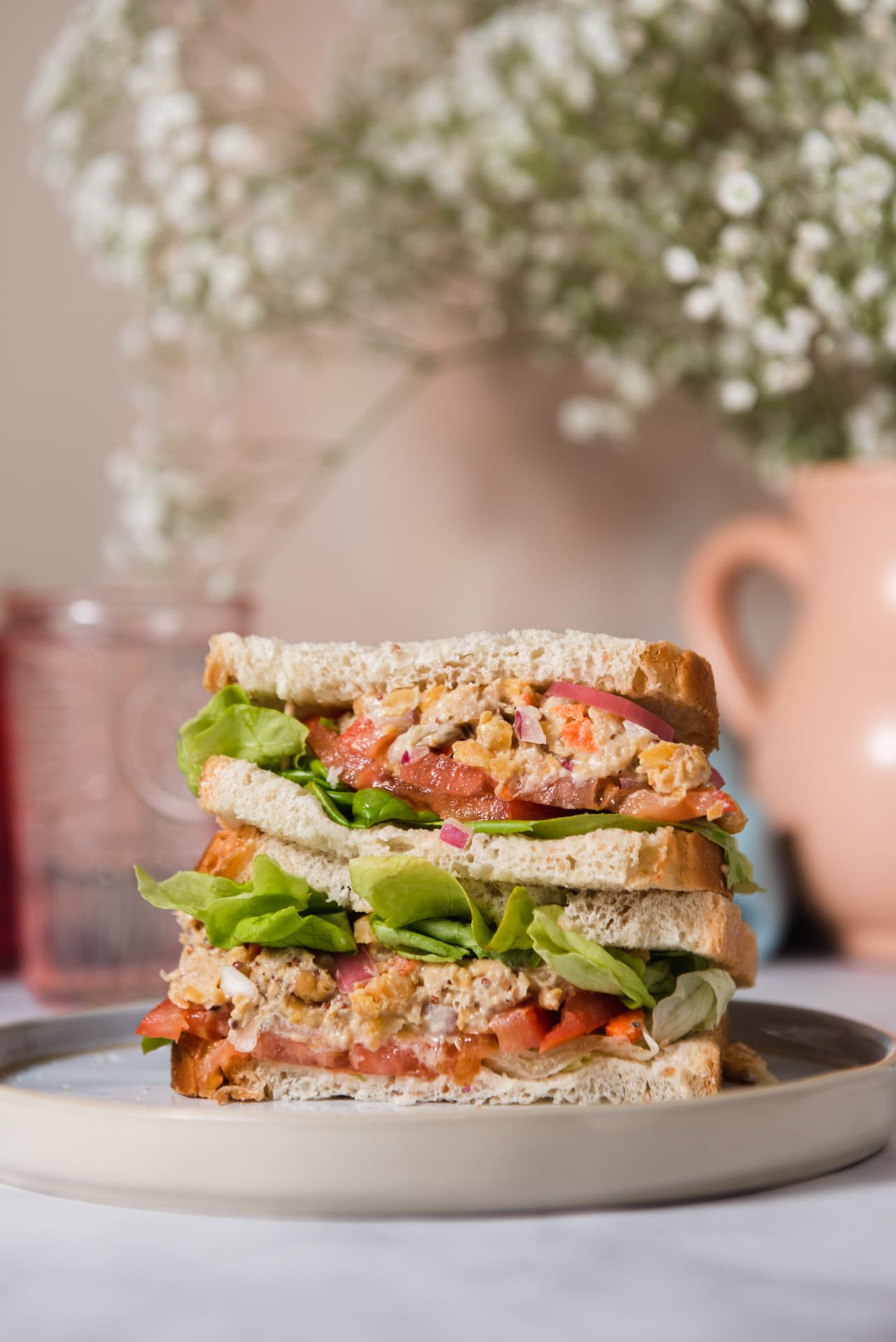 Double layered sandwich on plate with vase of flowers in the background