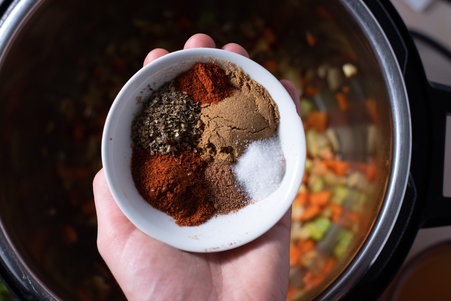 Hand holding small white bowl filled with spices and seasonings