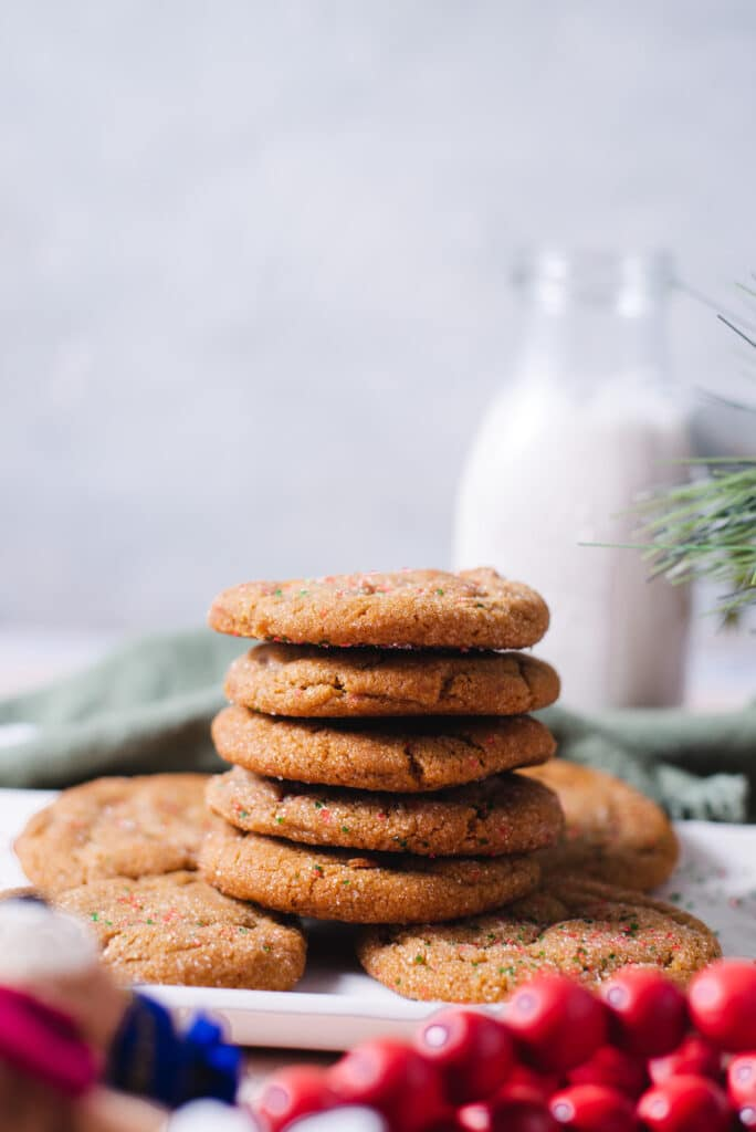 Side view of stack of five cookies with glass of milk in the background