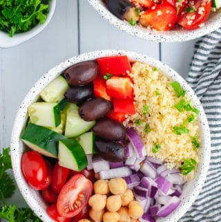 Overhead view of a colorful bowl of vegetables on a white wood background