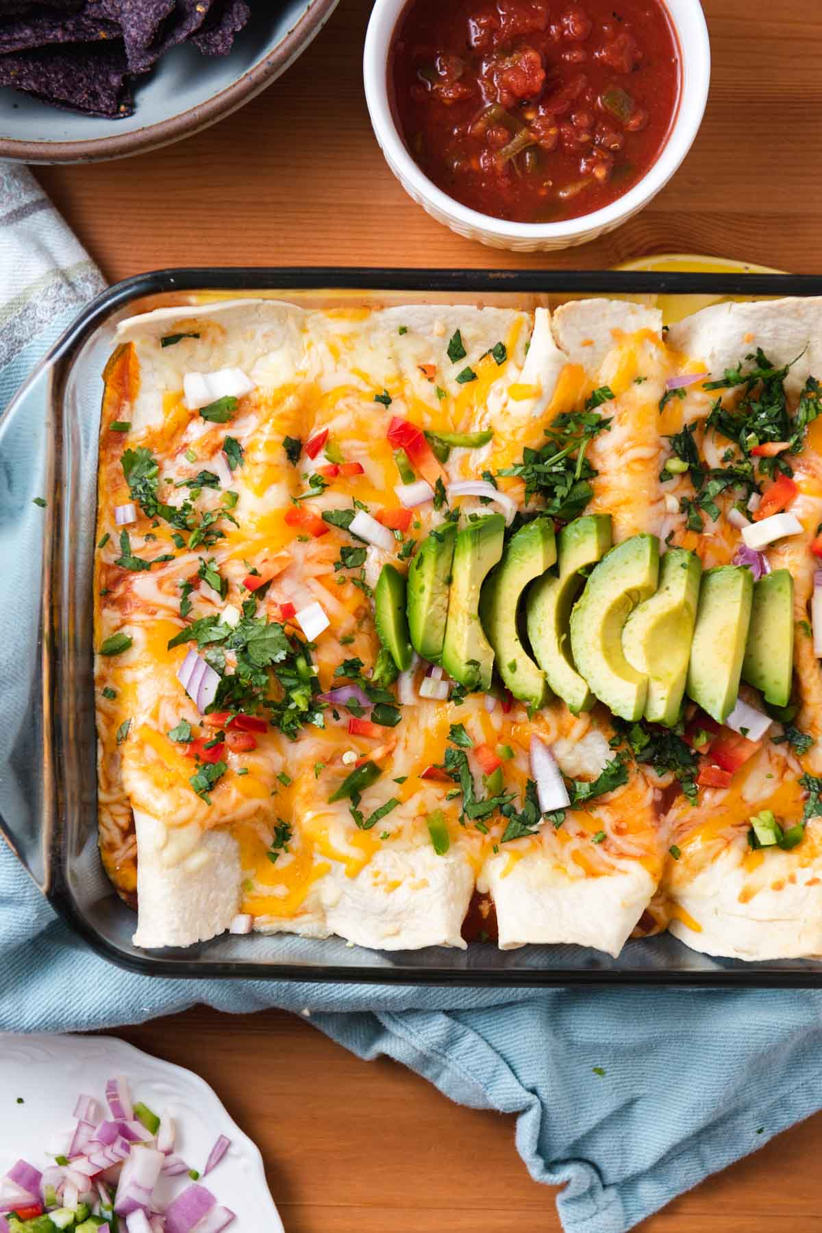 Overhead view of enchiladas topped with sliced avocado and cilantro