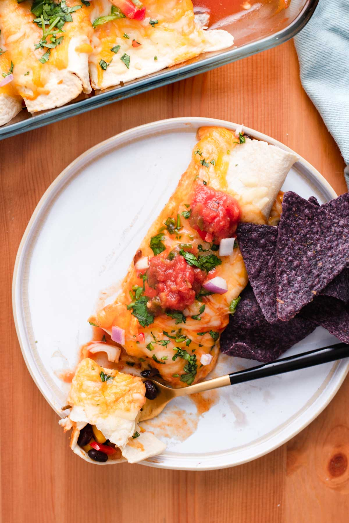 Enchilada on a white plate with purple tortilla chips