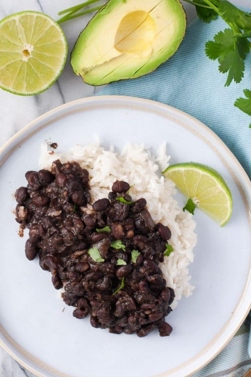 Black beans and white rice on a white plate with a lime wedge