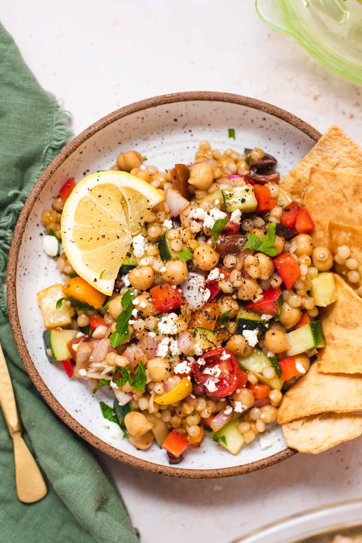 Overhead view of white bowl filled with couscous salad and a lemon wedge