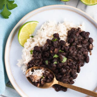 View from above of refried black beans and white rice on a plate with a lime