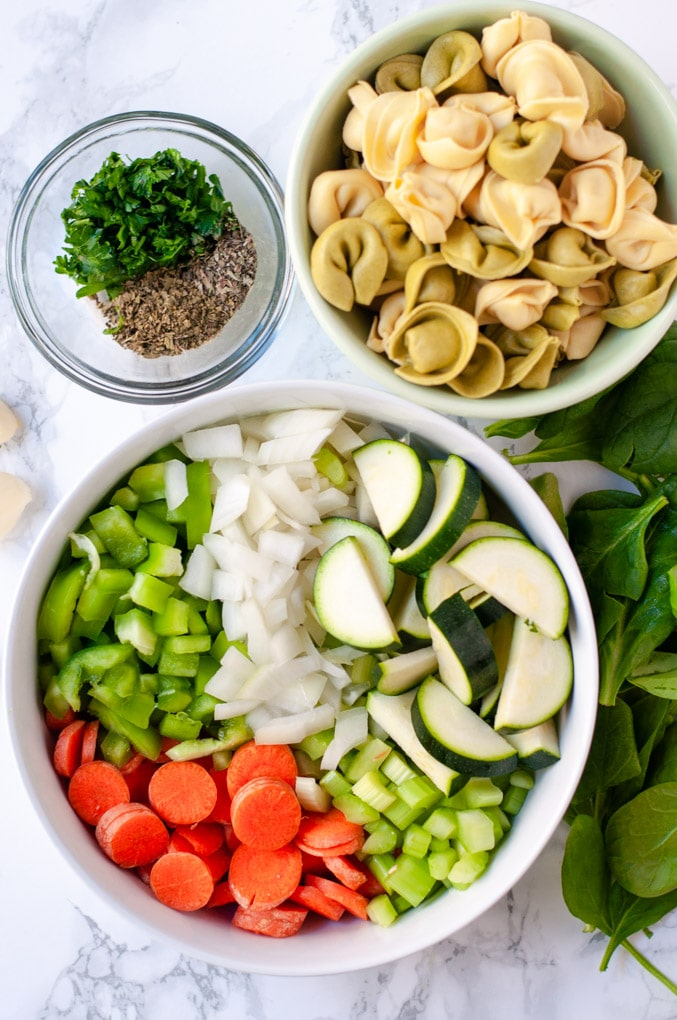 Bowls filled with chopped vegetables, tortellini and herbs
