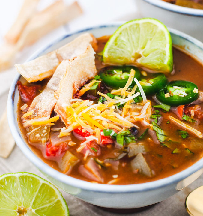 Close up of tortilla soup in a white bowl. Topped with tortilla strips, lime wedge, cheese, and jalapenos.