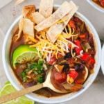 Overhead view of tortilla soup in a white bowl. A spoon containing a spoonful of soup sits on the bowl.