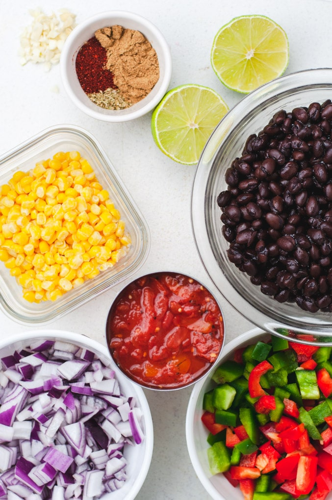 Separate containers holding ingredients to make tortilla soup: black beans, crushed tomatoes, bell pepper, red onion, corn, lime, spices and garlic.