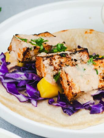 Close up of blackened tofu with a white coconut drizzle