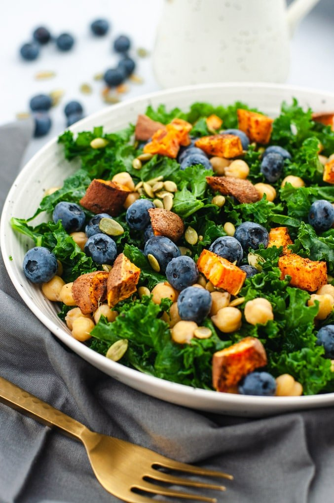 Close up of kale salad in a white bowl on a gray background.
