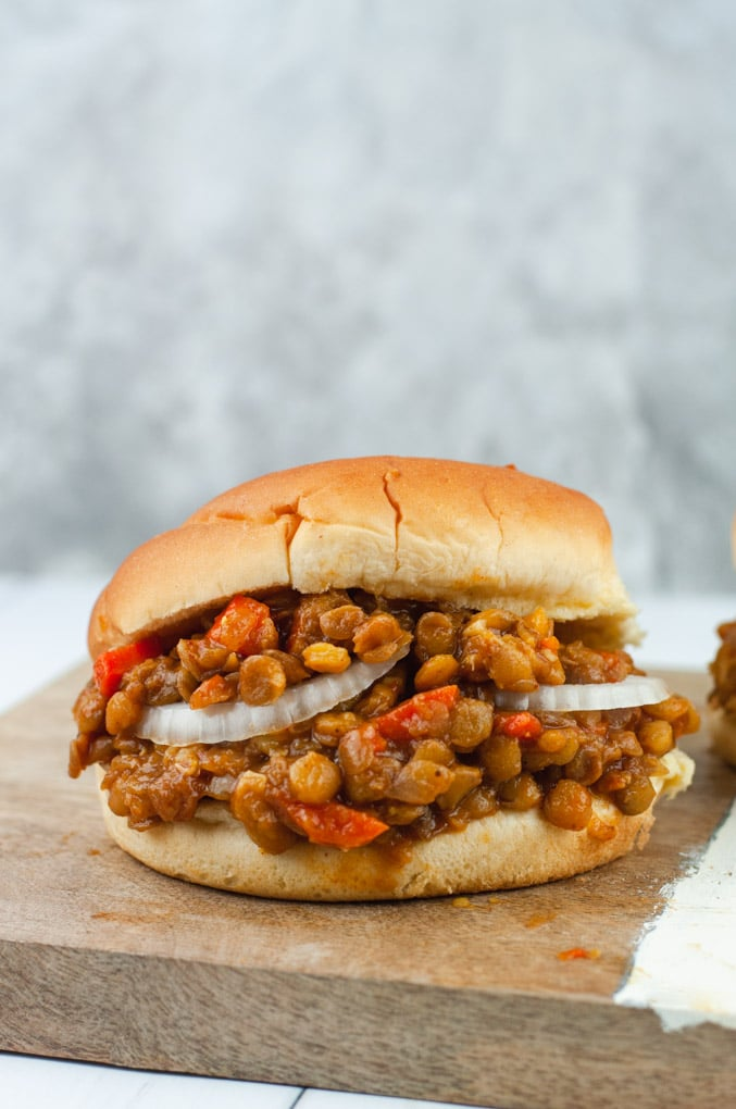 Burger overflowing with lentils and white onions
