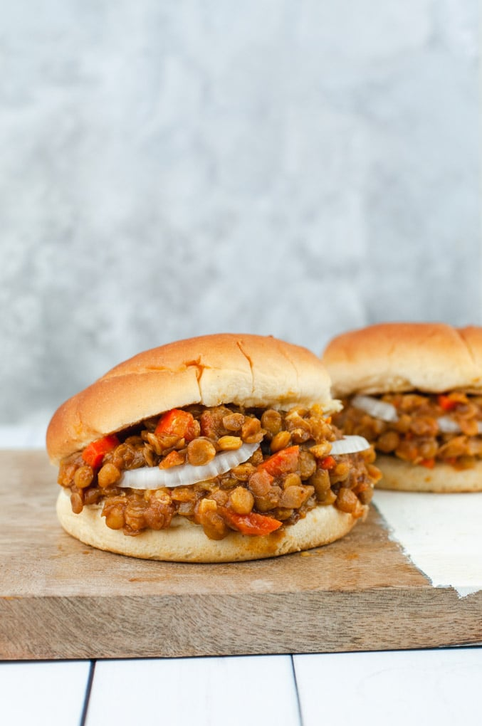 Two lentil sloppy joe sandwiches on a wooden cutting board