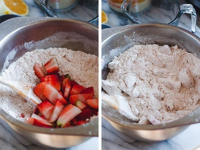 Strawberries being mixed into dry ingredients with a wooden spoon