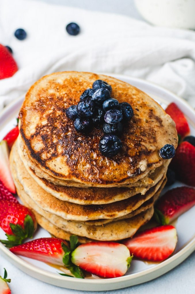 Overhead view of a stack of pancakes with blueberries on top. Pancakes are surrounded by strawberries and a white background.