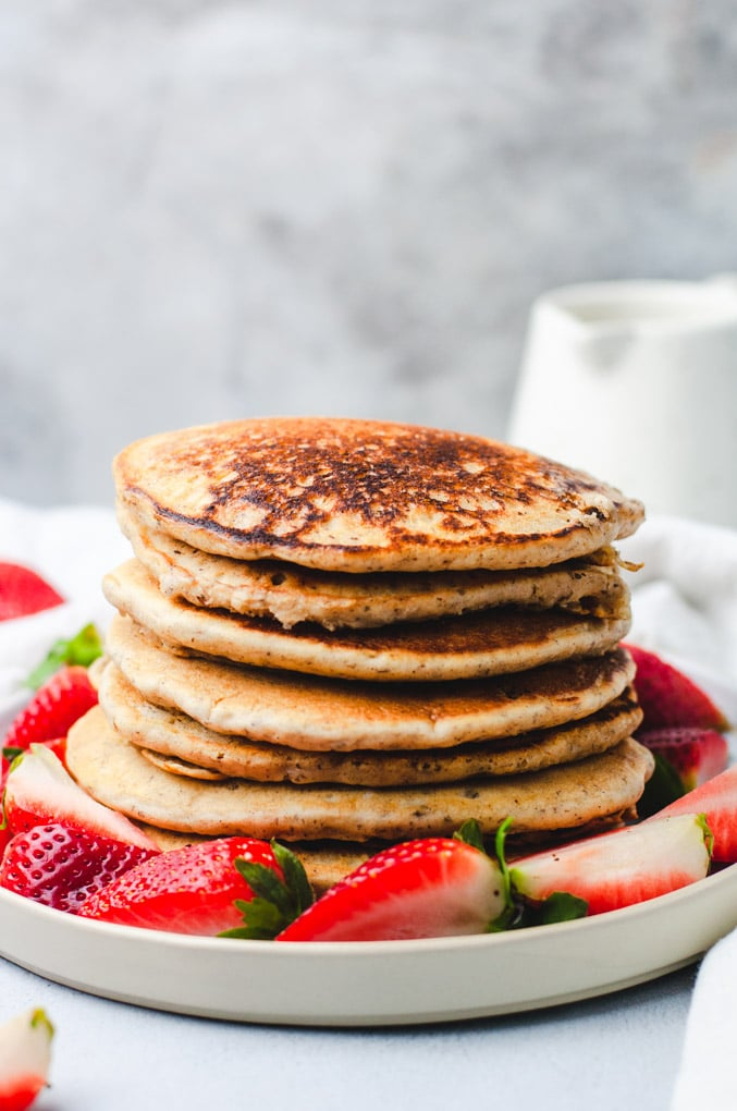 A stack of seven vegan pancakes on a white plate with sliced strawberries.