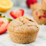 A single strawberry muffin in the foreground with more blurred muffins and strawberries in the background