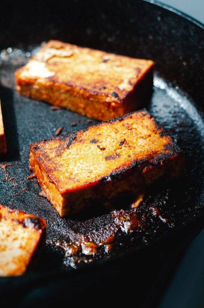 Crispy blackened tofu being pan fried in a cast iron pan.