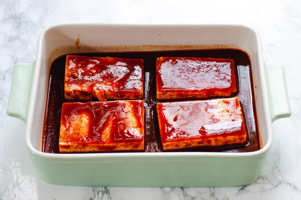 Four slice sof tofu covered in BBQ sauce marinade in a green baking dish.