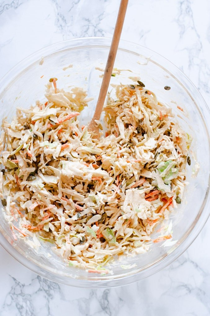 Tahini coleslaw in a large glass bowl on a marble background. A wooden spoon is resting in the bowl.