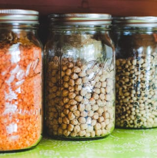 Ball jar filled with dry chickpeas next to two other jars sitting on a green shelf.
