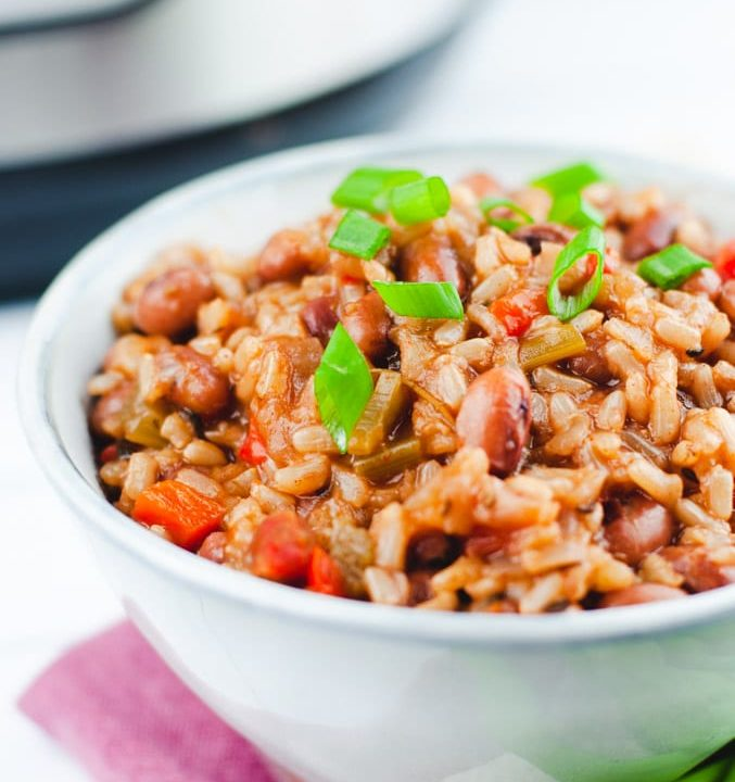 Close up of detail of brown rice and red beans. The bowl is sitting on a red checked tablecloth with an Instant Pot in the background.