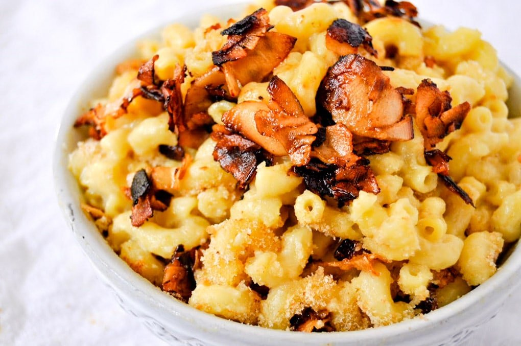 Close up of macaroni and cheese topped with red-orange bacon bits.
