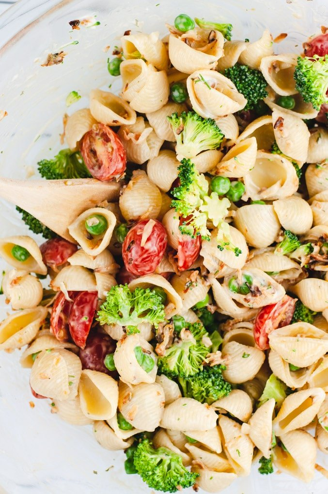 Close up view of pasta salad with broccoli, slices of cherry tomato, and peas.