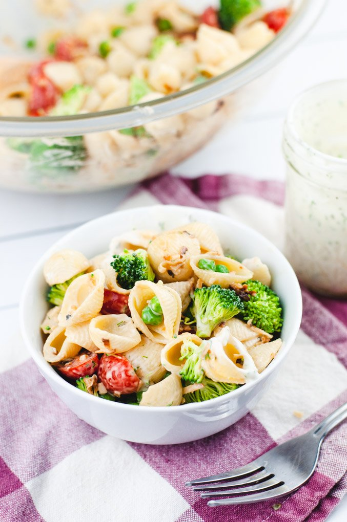 Side view of pasta salad in a white bowl on red checked cloth