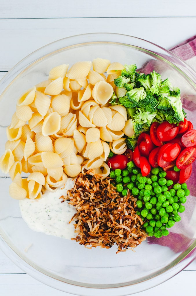 A large glass bowl filled with ingredients used to make pasta salad