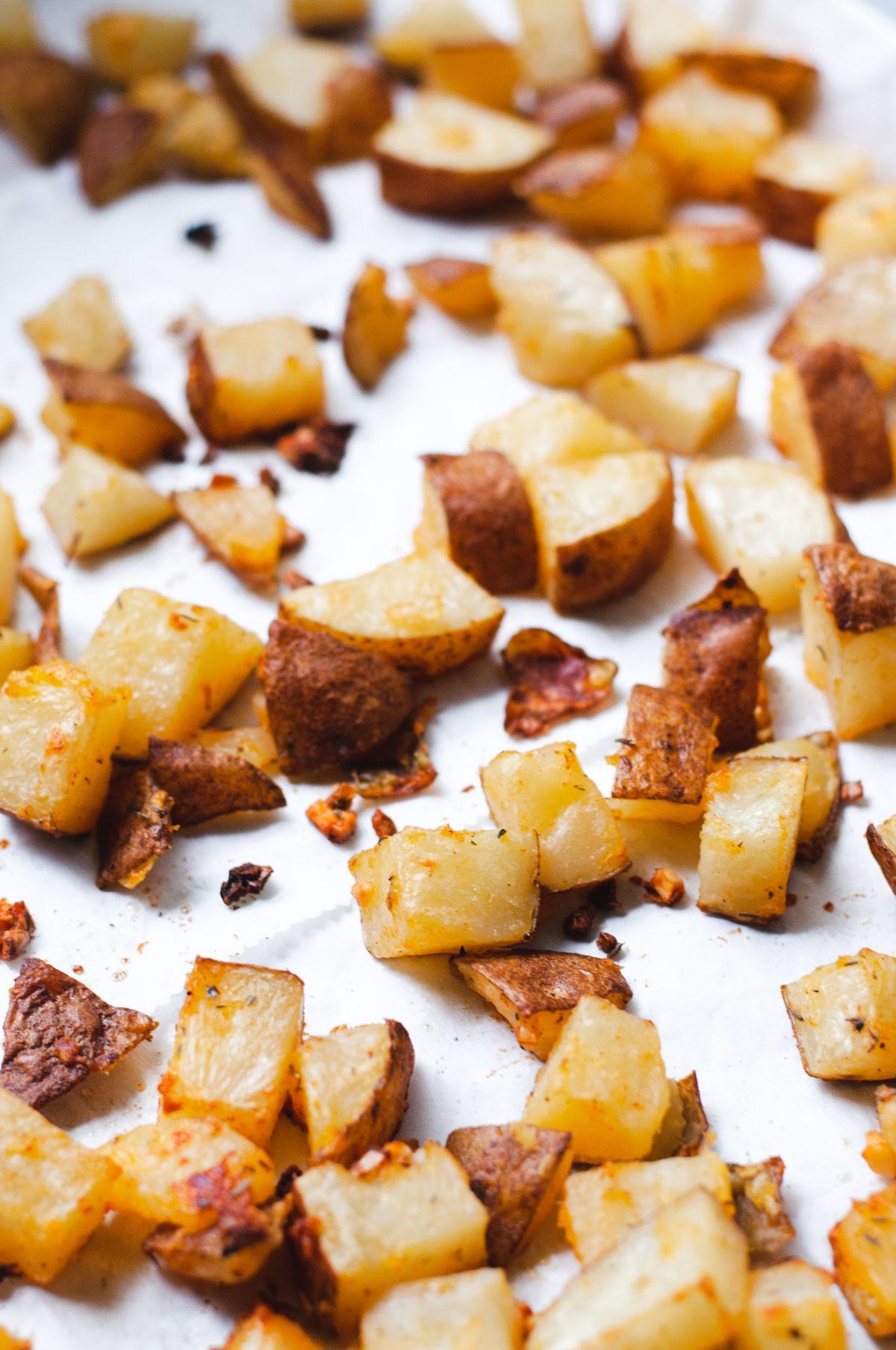 Crispy potatoes on a parchment paper lined sheet pan