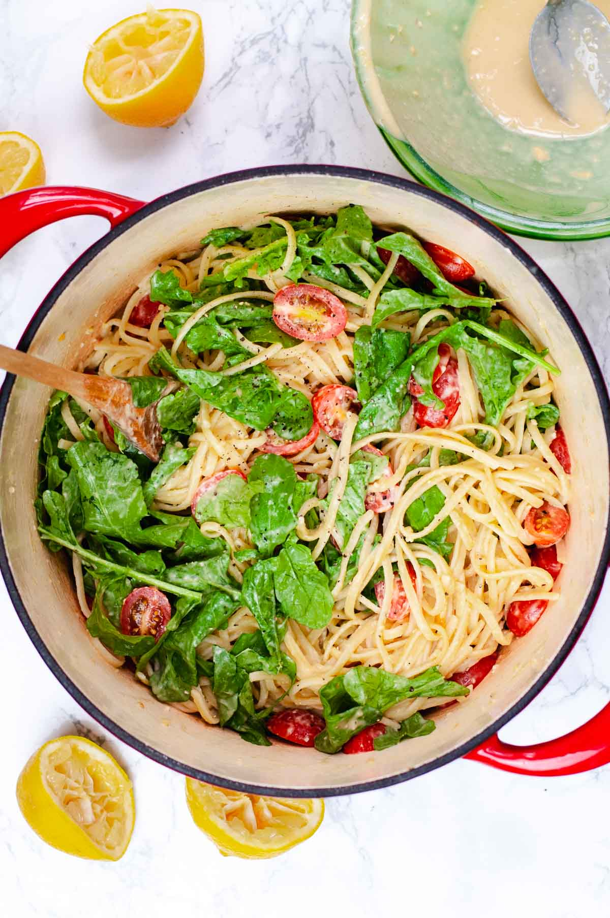 Overhead view of red dutch oven filled with hummus pasta, arugula and sliced tomatoes