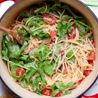 Overhead view of hummus pasta with lemon, cherry tomatoes, and arugula. A wooden spoon is resting in the large red pot.