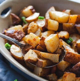 Close up view of the crispy potatoes being scooped with a spoon.
