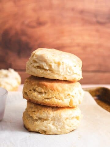 Three vegan biscuits stacked on top of each other in front of a wood background
