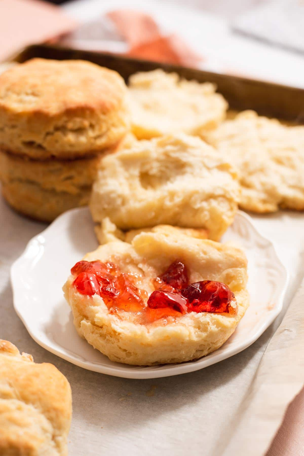 Jam spread on a biscuit half on a white plate with more biscuits in the backgroun