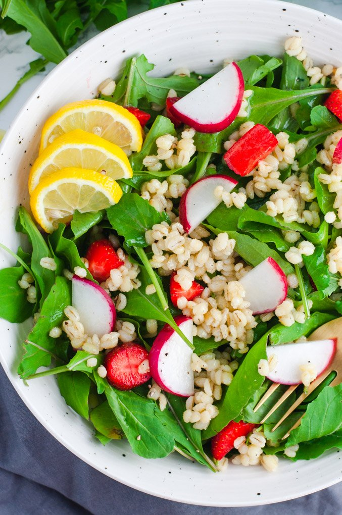 Overhead view of arugula salad topped with lemons, radishes, strawberries and pearl barley.