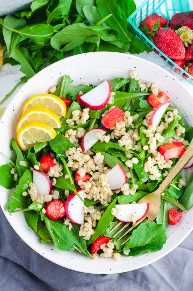Overhead view of arugula salad with a gold fork resting on the side.
