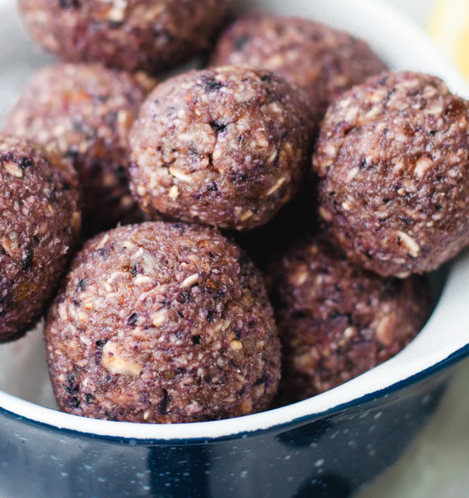 A blue bowl filled with blueberry lemon energy balls.