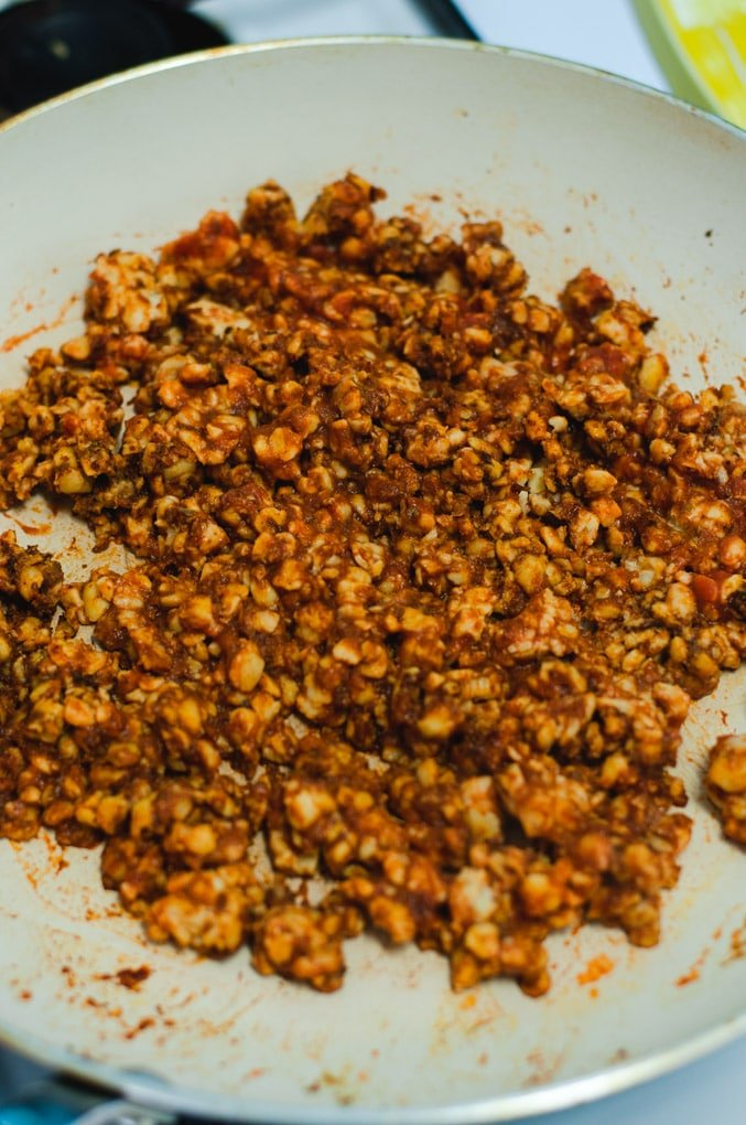 Browned tempeh taco meat being sauted in a white skillet.