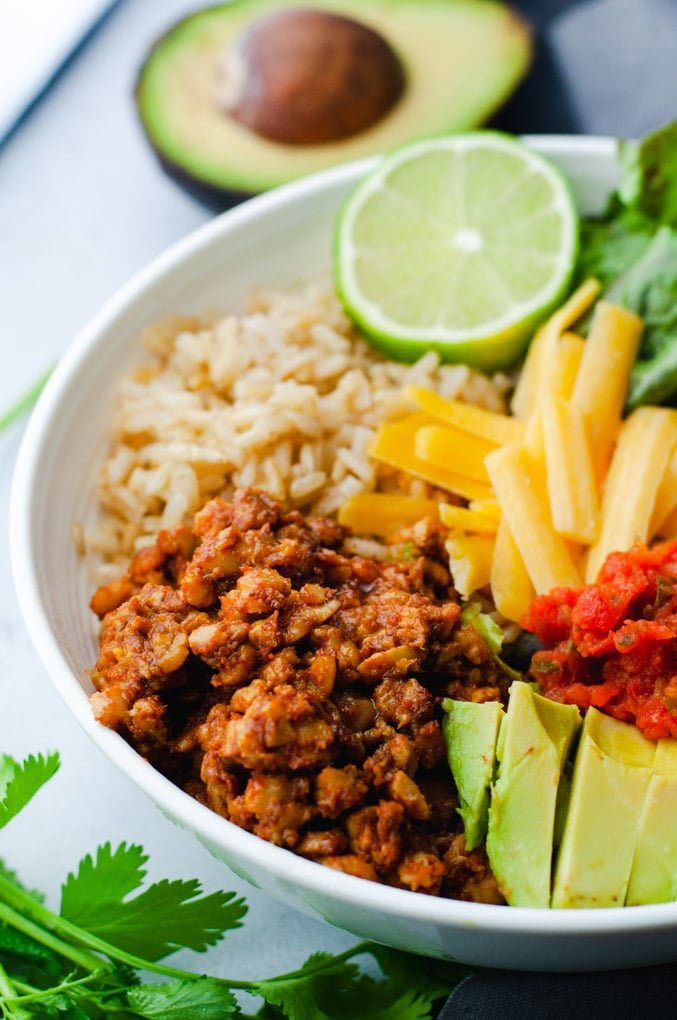 A burrito bowl containing tempeh taco meat, rice, cheese, salsa, avocado, and lime. The focus is on the tempeh.