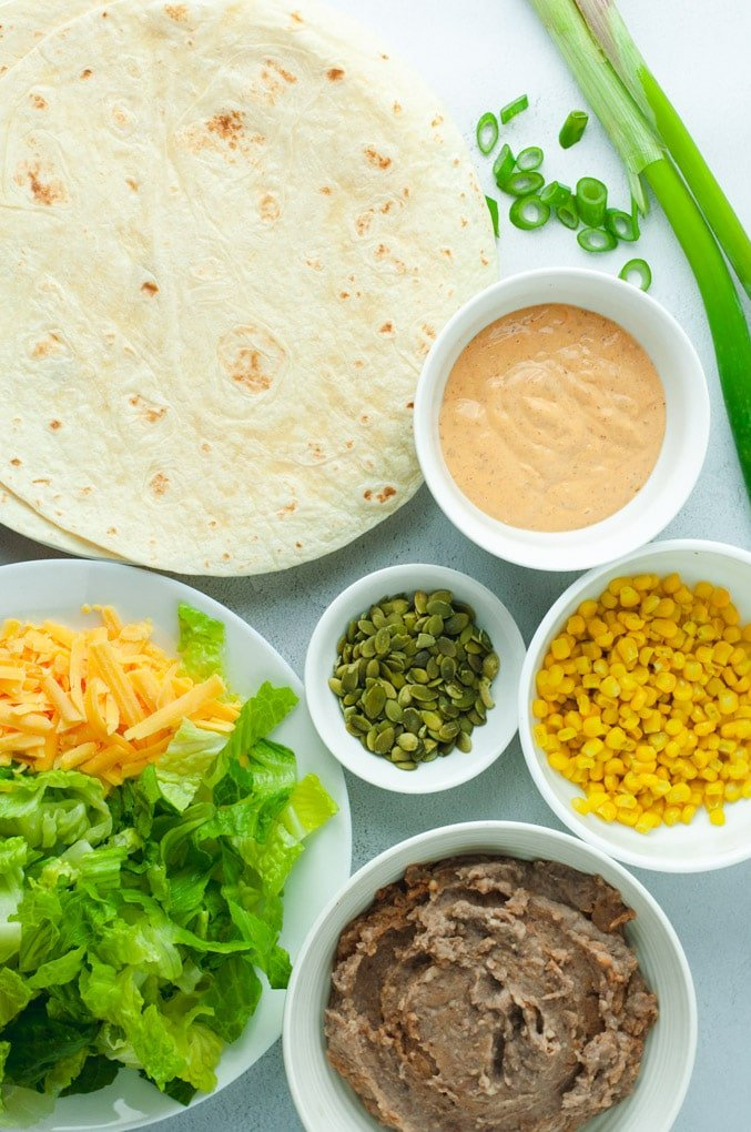 Overhead view of ingredients used to make vegetarian bean burritos: lettuce, cheese, tortillas, pumpkin seeds, corn, beans, and chipotle sauce.